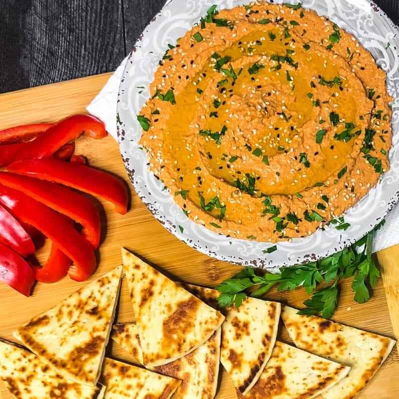 Overhead shot of Roasted Red Pepper Walnut Hummus garnished with red pepper slices and pita bread.