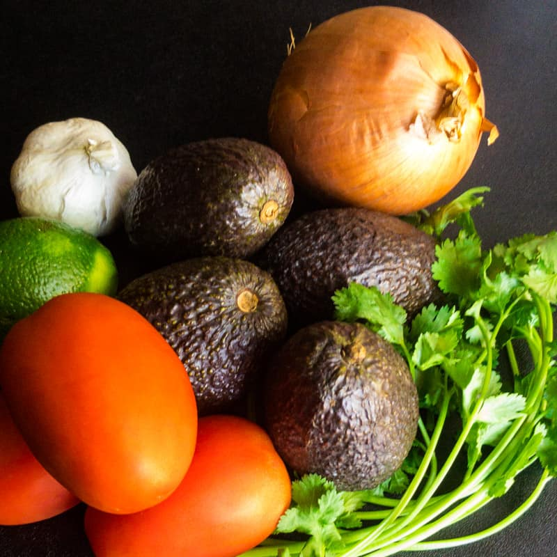 Ingredient photo showing whole avocados, tomatoes, onion, lime, garlic, and cilantro.