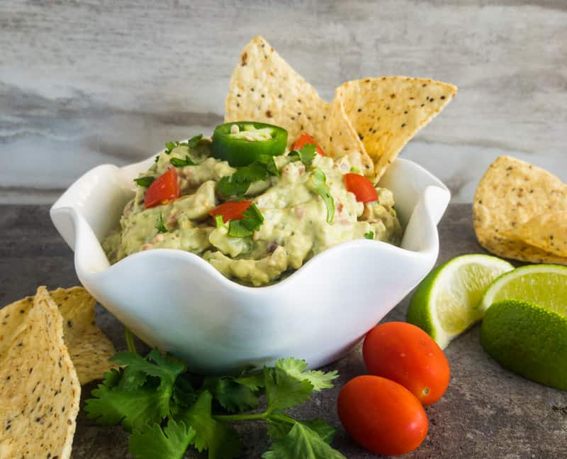 Easy Guacamole in a white bowl garnished with tomato, jalapeno, lime, cilantro.