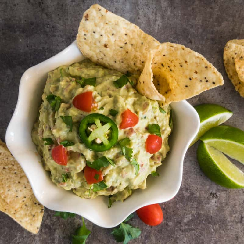Overhead shot of Easy Guacamole in a white bowl garnished with corn chips, tomato, jalapeno, cilantro and lime.