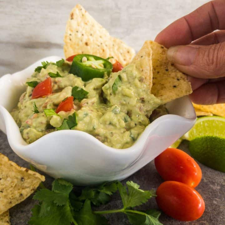 Easy Guacamole in a white bowl garnished with tomato, jalapeno, lime, cilantro; with a had dipping a corn chip.