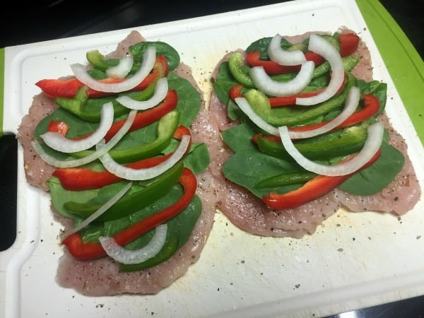 Chicken breasts on a cutting board topped with spinach, peppers, and onions.