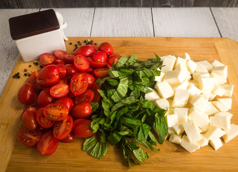 Halved tomatoes, chopped basil, and cubed mozzarella on a wood cutting board with a salt box and black peppercorns in the background.