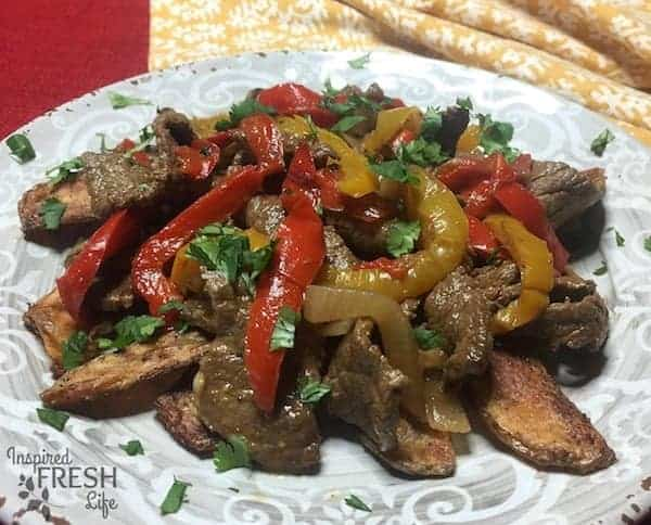 Lomo Saltado on a grey plate topped with fresh cilantro leaves