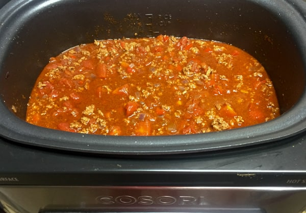 Tomatoes, spices, and broth added to the meat, red peppers, and onion.