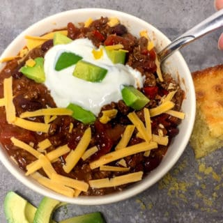 Slow cooker chili in a white bowl topped with shredded cheese, sour cream, and avocado with corn bread on the side.