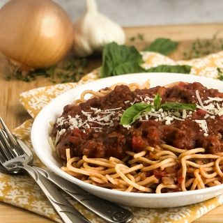 Close up shot of Ragu over spaghetti garnished with basil and parmesan in a white bowl.