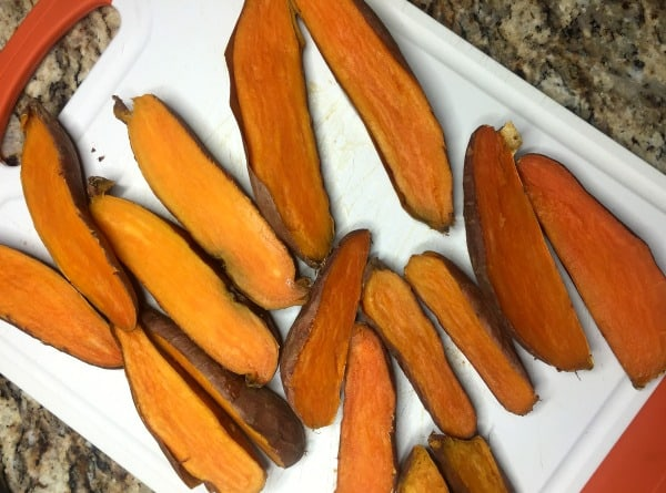 Cooked sweet potatoes cut in half on a cutting board