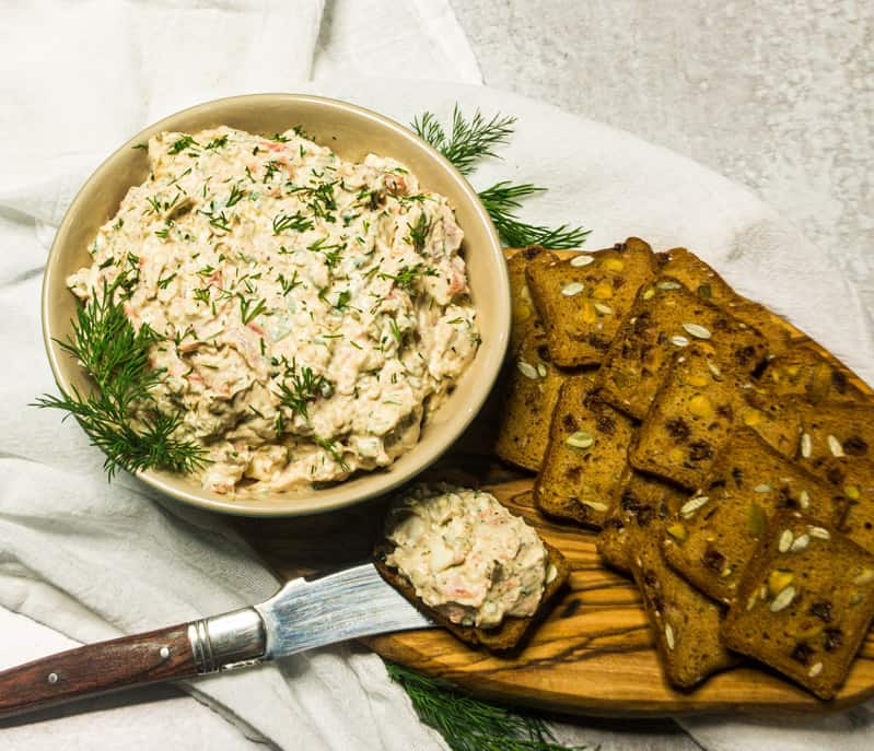 Overhead shot of Smoked Salmon Dip garnished with fresh dill with crackers to the side.