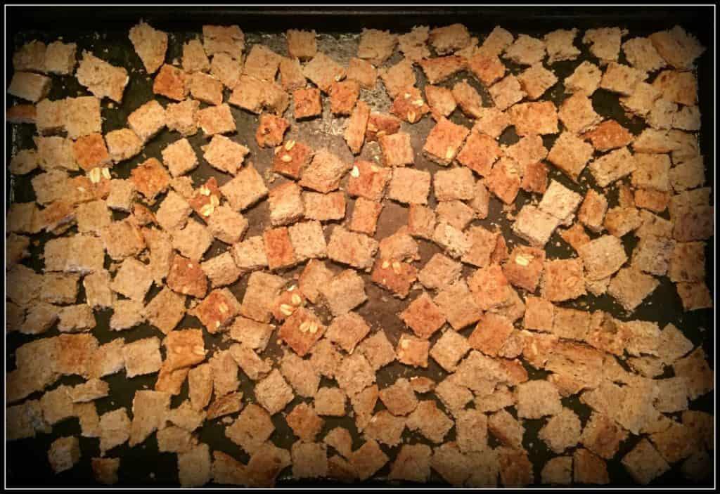 Gluten-free bread cubes on a baking sheet.