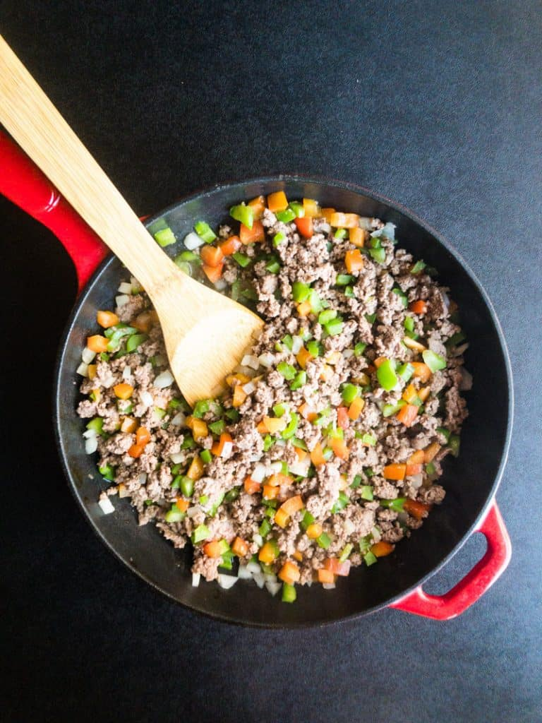 Ground beef in a skillet with peppers and onoins