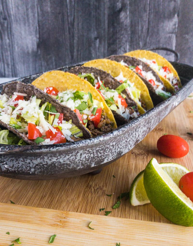 Head on shot of taco meat in blue and yellow corn shells on a tin platter.