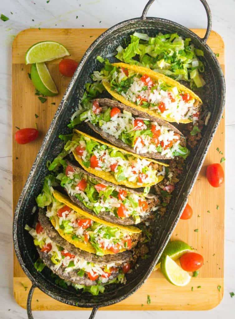 Overhead shot of blue and yellow shell tacos on a tin platter resting on a wood cutting board, garnished with tomatoes and lime wedges.