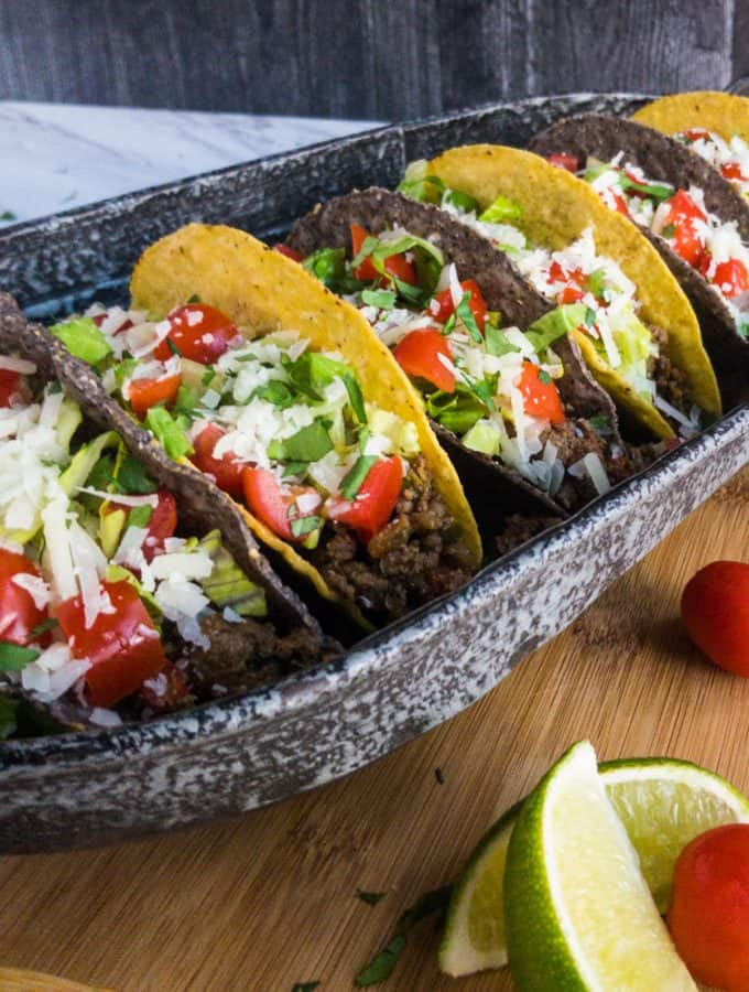 Close up of tacos in blue and yellow corn shells with tomatoes and lime wedges as garnish.