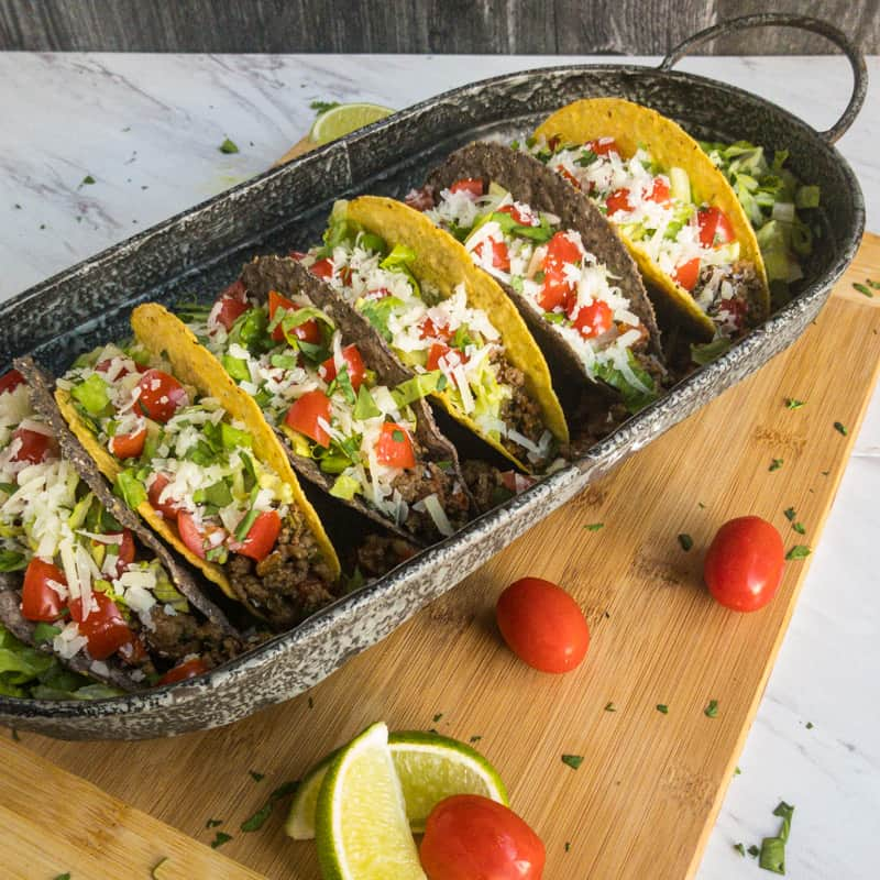 Full platter view of tacos in yellow and blue corn shells in a tin platter on a wood cutting board with tomato and lime wedge garnish.