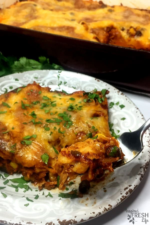 Chicken enchilada casserole on a plate with a fork lifting a bite