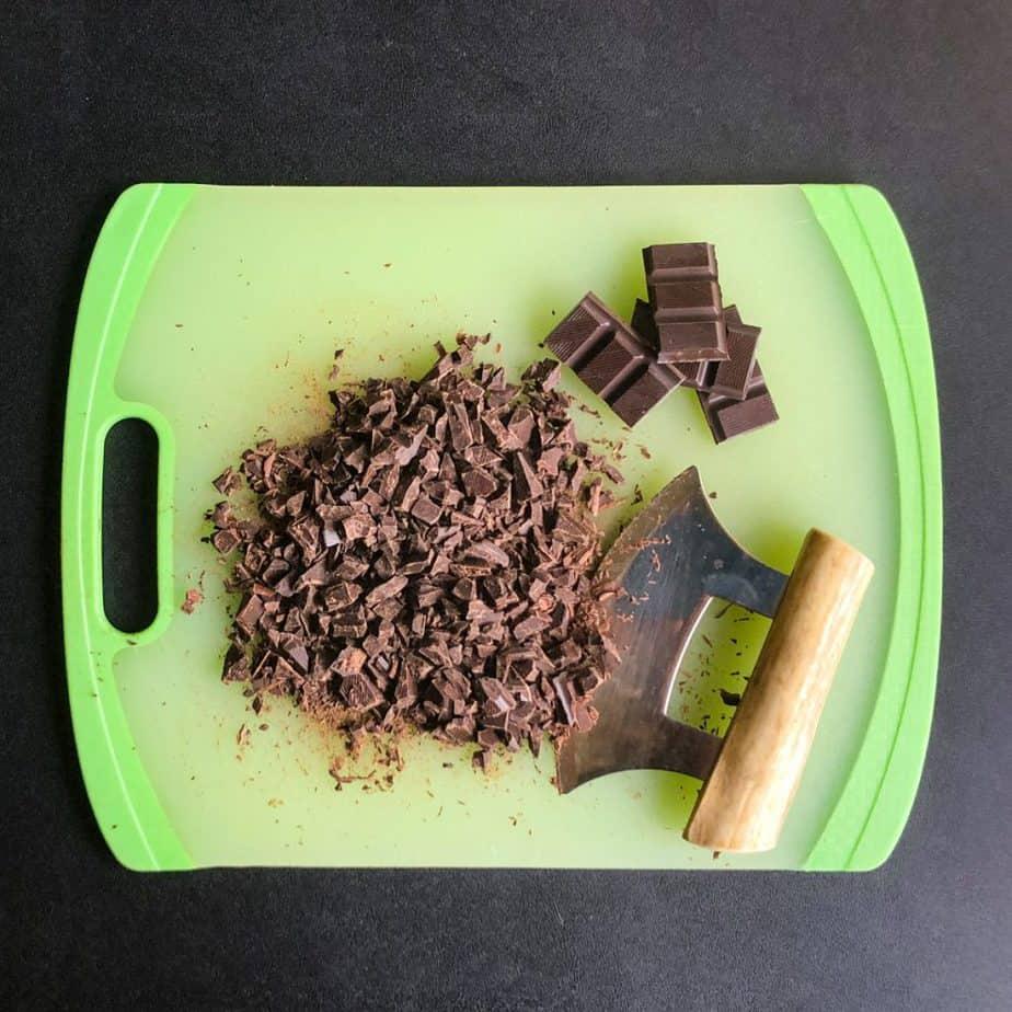 Finely chopped dark chocolate bar with an ulu knife on a green cutting board.