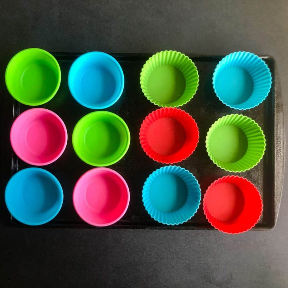 Empty mulit-colored silicone baking cups on a sheet tray.