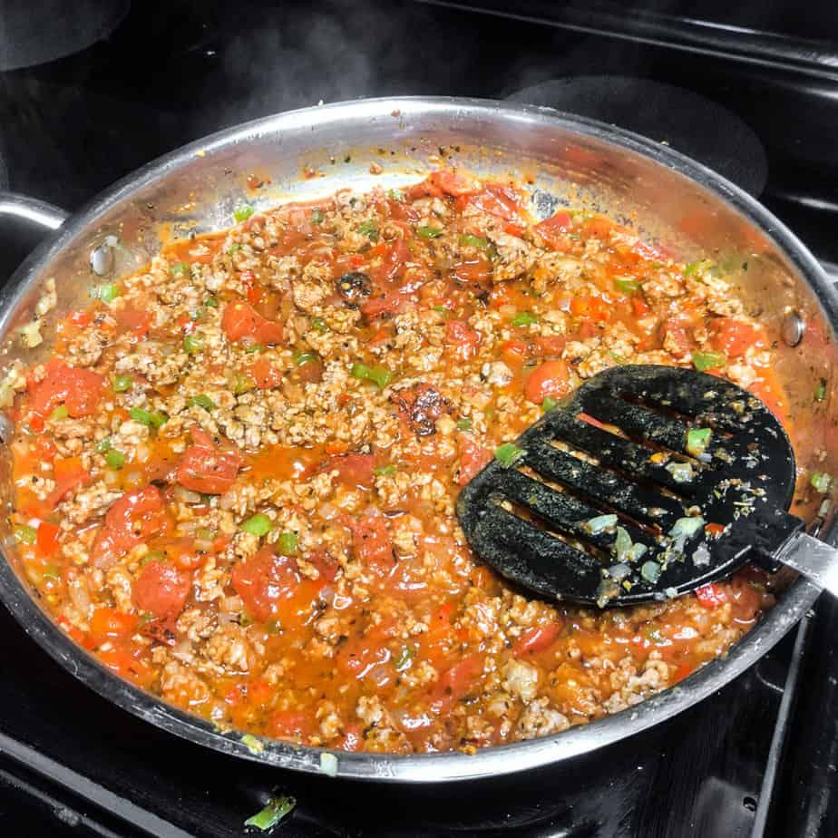Sloppy Joe mixture simmering in a stainless steel skillet.