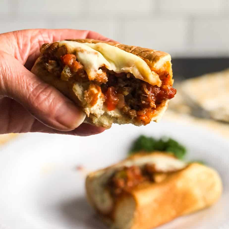 Hand holding an Italian Sloppy Joe with a bite out of it.