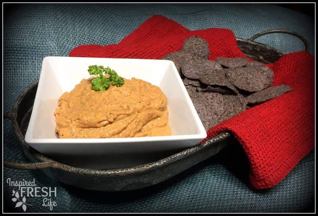 Black Bean Hummus in a white bowl with blue corn tortilla chips