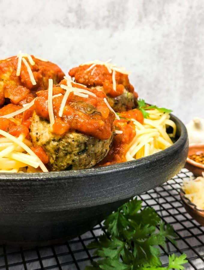 Close up shot of turkey meatballs nestled into spaghetti, topped with marinara sauce, in a black bowl.
