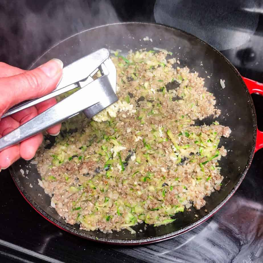Hand holding garlic press to add minced garlic to the skillet.