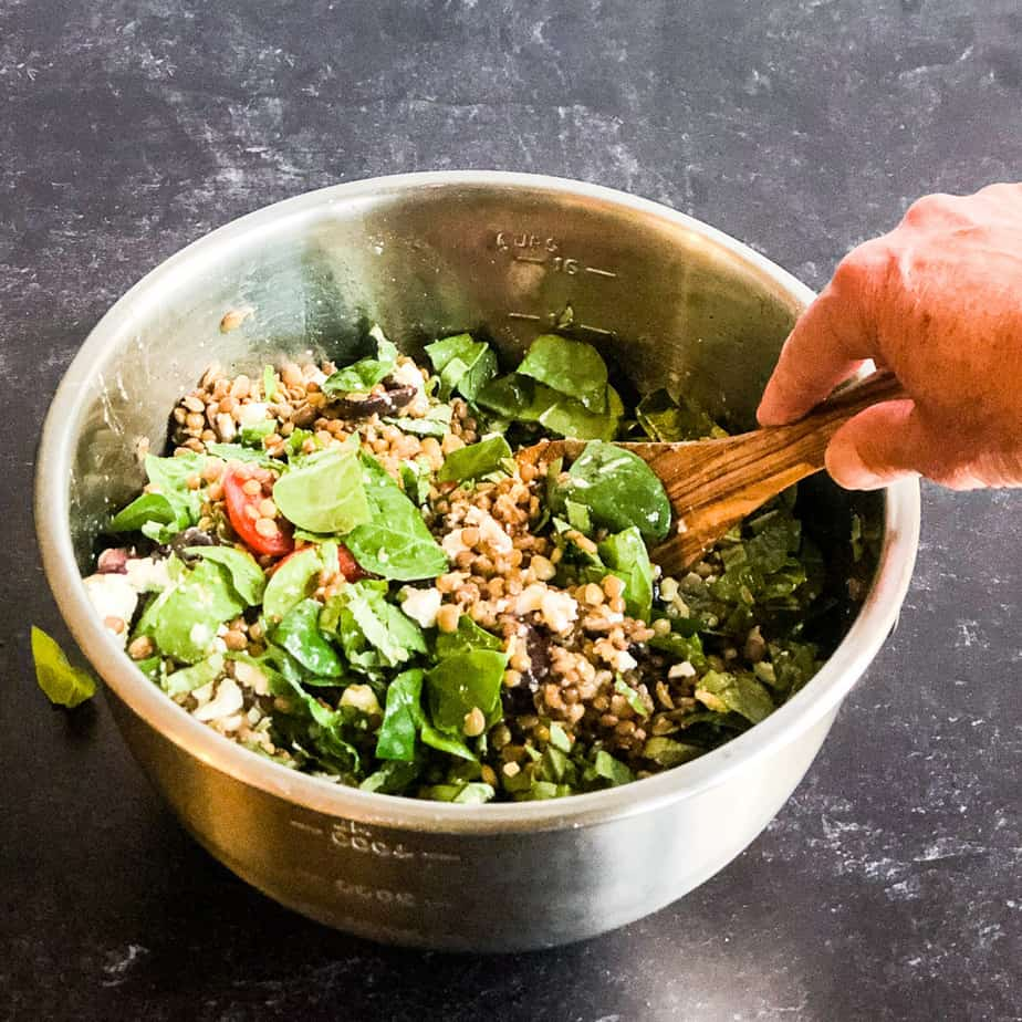 Mixing the salad ingredients in a large stainless steel bowl.
