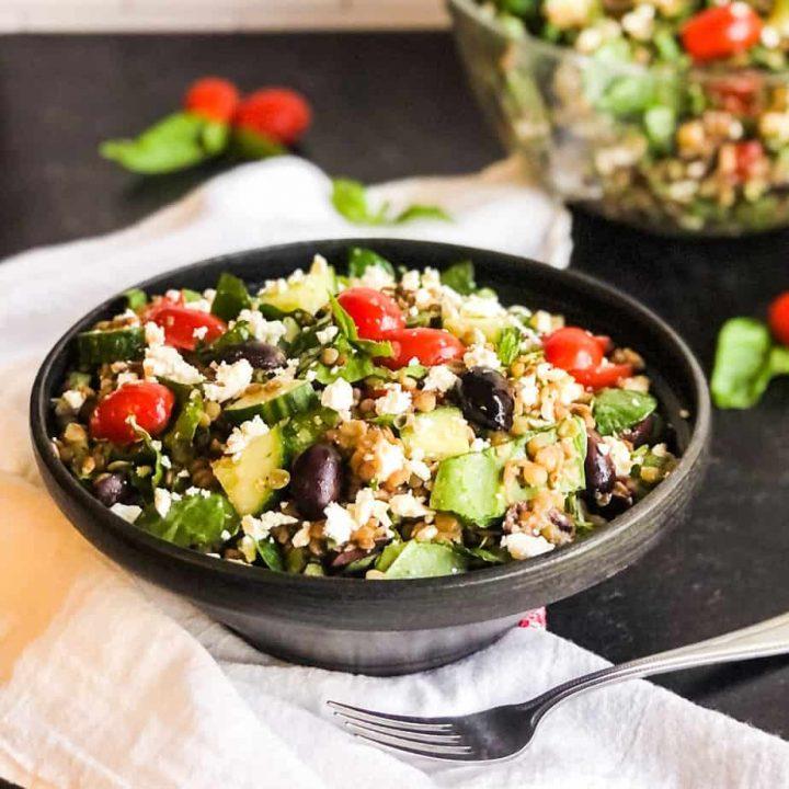 Close up shot of Greek Lentil Salad in a black bowl.