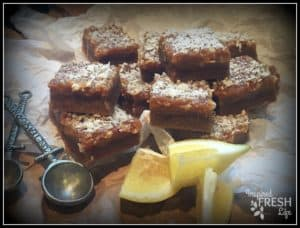 Luscious Lemon Squares cut and sitting on crumpled parchment paper with lemon accents and measuring spoons.