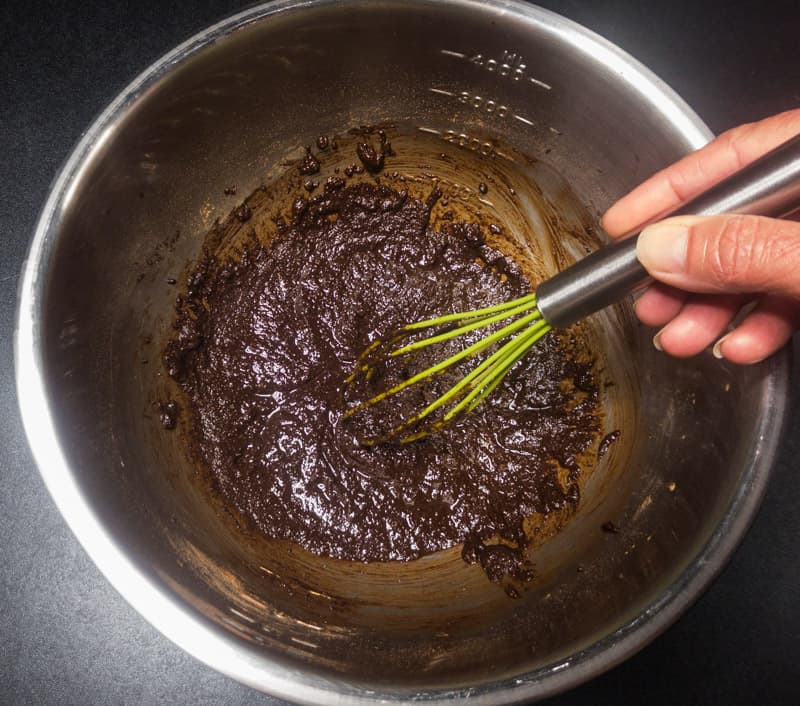 Mixing the melted butter, coconut sugar, and cacao powder in a stainless steel bowl.