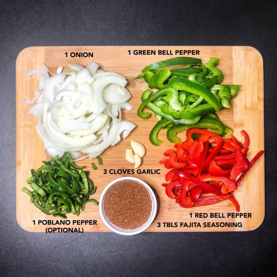 Ingredients for Steak Fajitas prepped and portioned on a wood cutting board.