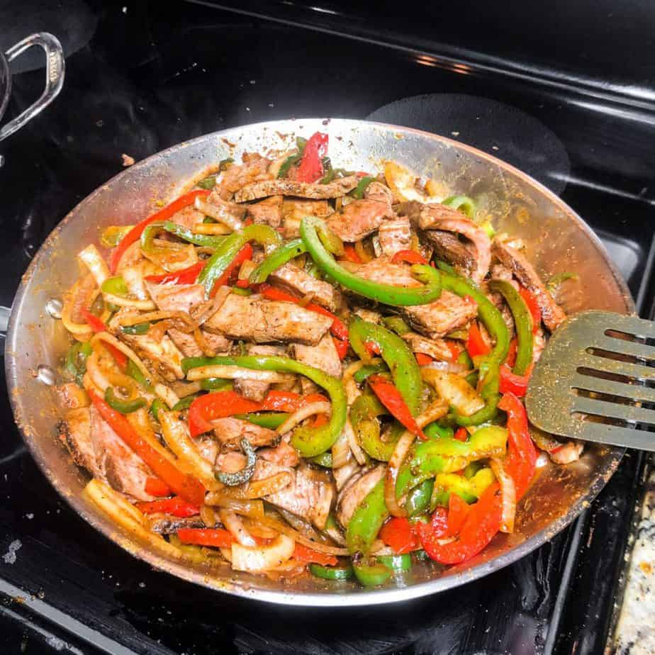 Steak cooking with peppers and onions in a stainless steel skillet.