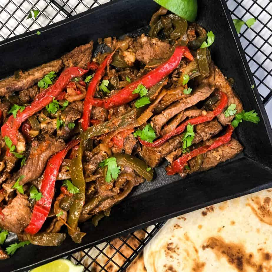 Overhead shot of Steak Fajitas on a black plate garnished with cilantro and tortillas in the foreground.