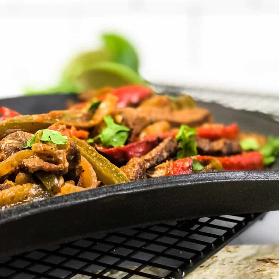 Side shot of Steak Fajitas on a black plate with lime wedges blurred in the background.