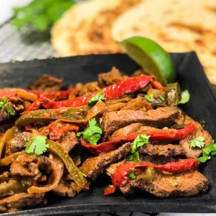 Close up shot of Steak Fajitas on a black plate garnished with lime wedge and cilantro.