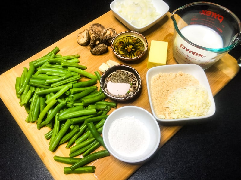 Ingredients for Green Bean Casserole on a wood cutting board.