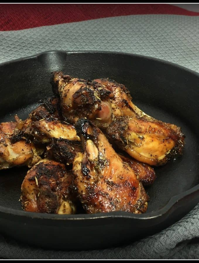 Smoked Rosemary Wings in a cast iron skillet on a grey towel.