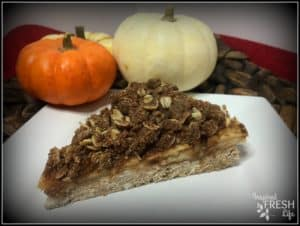 slice of snickerdoodle apple crisp on a white plate with mini pumpkins in the background