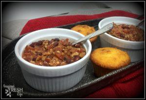 two bowls of slow cooker turkey chile in white bowls on a tin platter with cornbread muffins