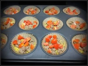 Spaghetti squash, sausage, and chopped tomatoes in parchemnt lined muffin tin.