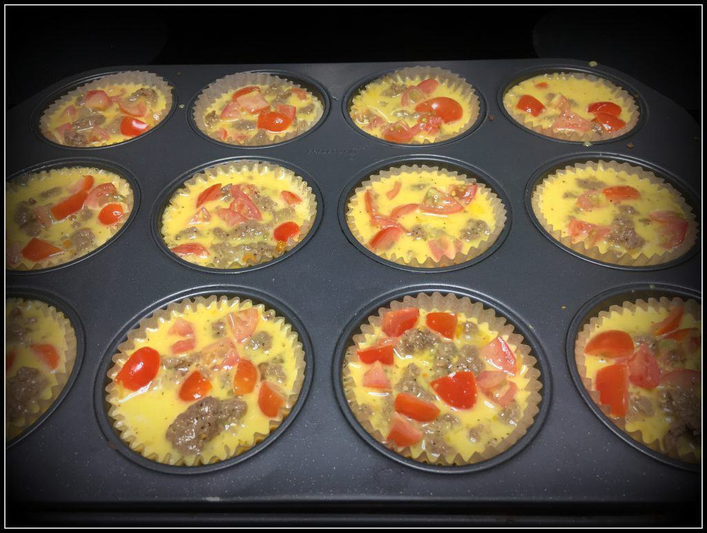 Muffin tins full of egg mixture, sausage and veggies, ready to bake in the oven.