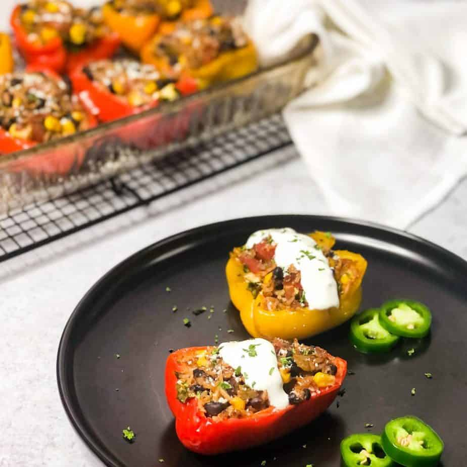 Overhead shot of stuffed peppers on a black plate garnished with crema, jalapenos, and cilantro with blurred baking dish in background.