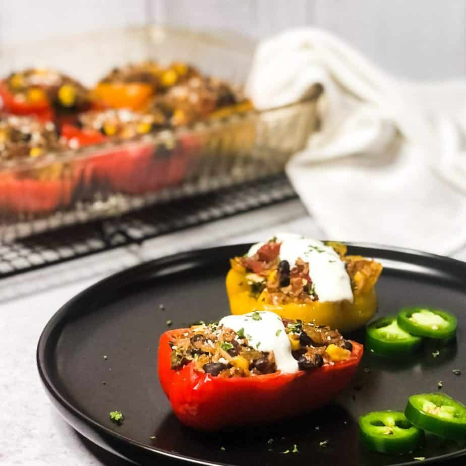 Side shot of stuffed peppers on a black plate garnished with crema, jalapenos, and cilantro with blurred baking dish in background.