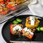 Close up shot of stuffed pepper cut in half with blurred baking dish of remaining peppers in background.