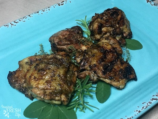 Grilled Garlic Sage Chicken Thighs on blue platter with fresh herbs