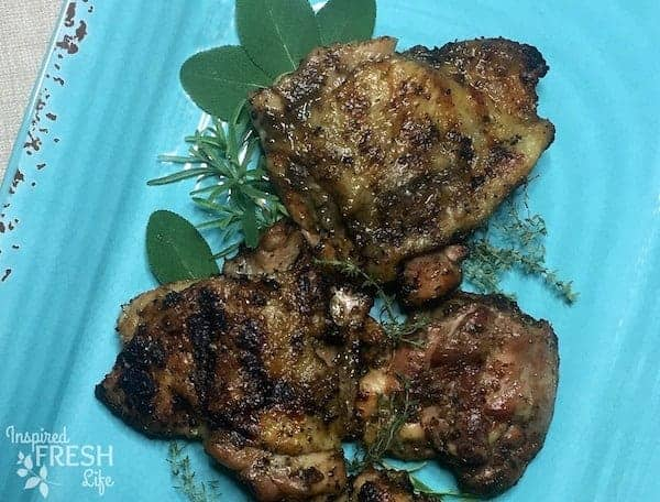 Grilled Garlic Sage Chicken Thighs on blue platter with fresh herbs