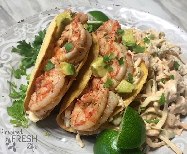 grilled shrimp tacos with cabbage slaw on a plate with lime wedges