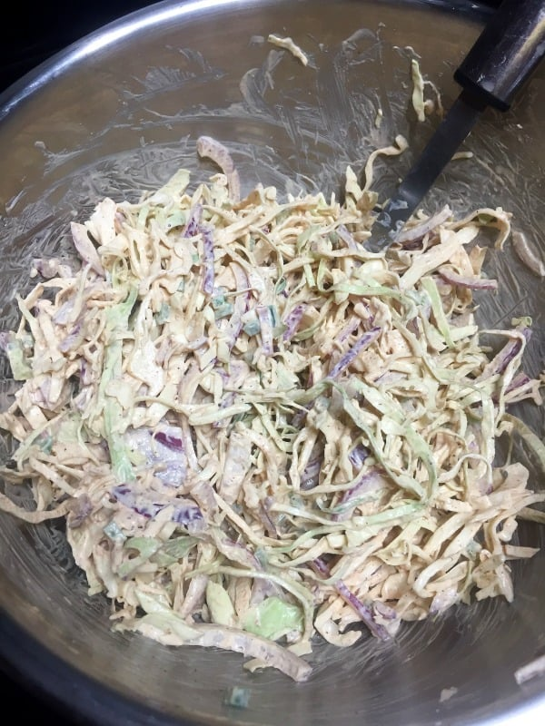 cabbage slaw mixed wtih sauce in a stainless steel bowl