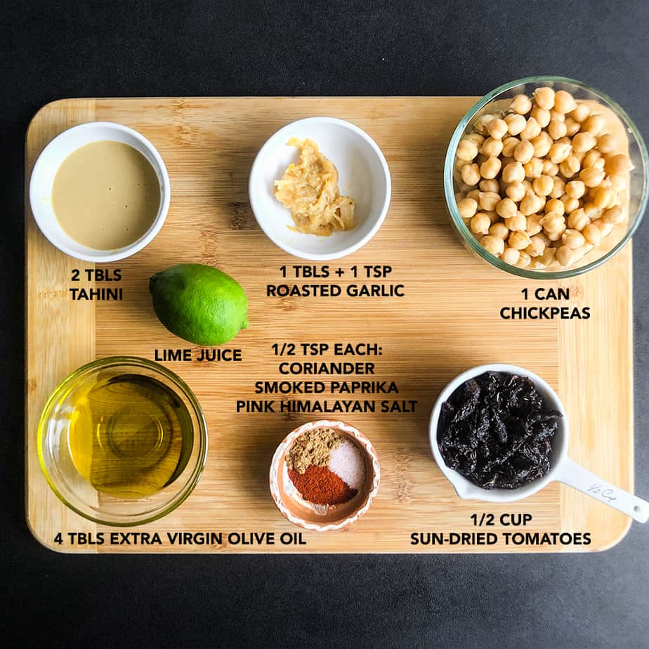 Hummus ingredients portioned on a wood cutting board.